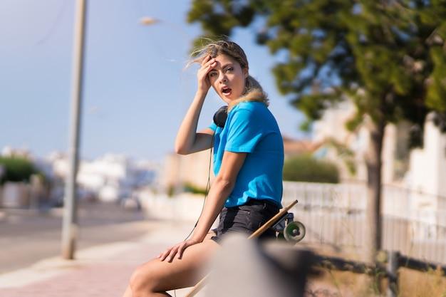 驚きの表情で屋外でスケートを持つティーンエイジャーの女の子