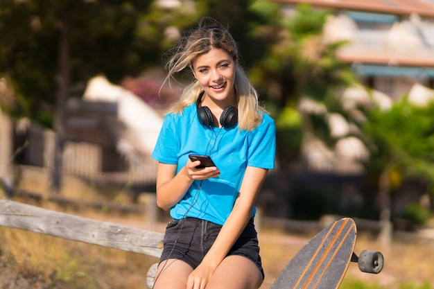 Teenager girl with skate at outdoors surprised and sending a message
