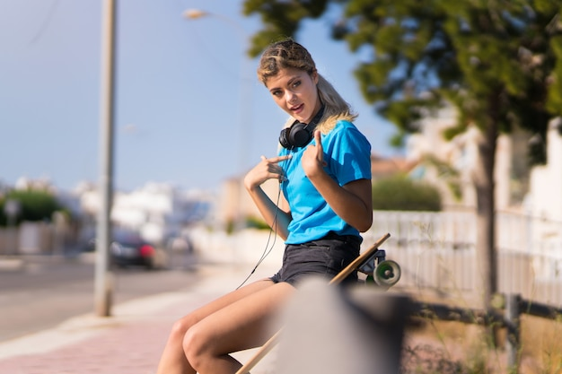 Teenager girl with skate at outdoors with surprise facial expression