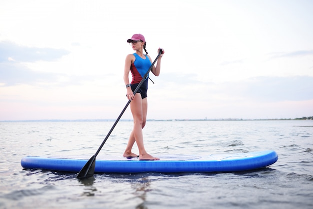 Teenager girl with sup board on the sea. paddle surf activity