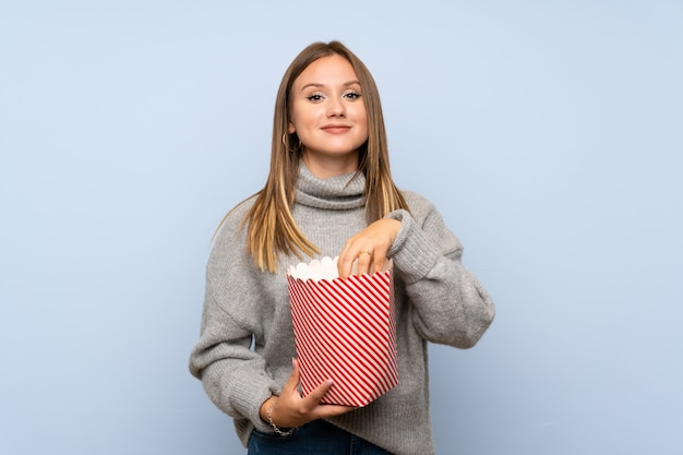 Teenager girl with sweater holding a bowl of popcorns