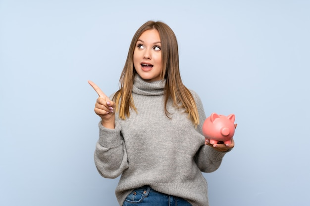 Teenager girl with sweater over isolated blue holding a big piggybank