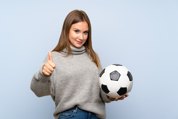 Teenager girl with sweater over isolated  holding a soccer ball