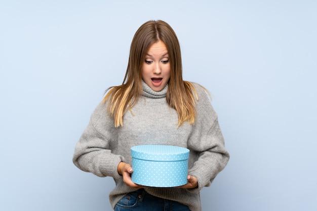 선물 상자를 들고 고립 된 파란색 배경 위에 스웨터와 십 대 소녀
