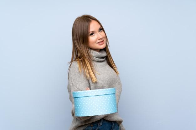선물 상자를 들고 고립 된 파란색 스웨터와 십 대 소녀