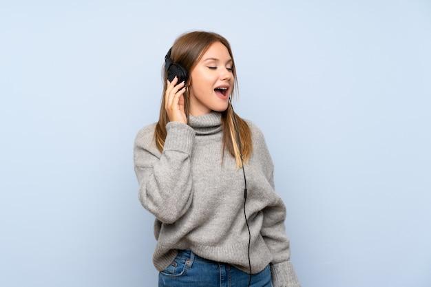 Девушка подростка с свитером над изолированным голубым слушая к музыке с наушниками