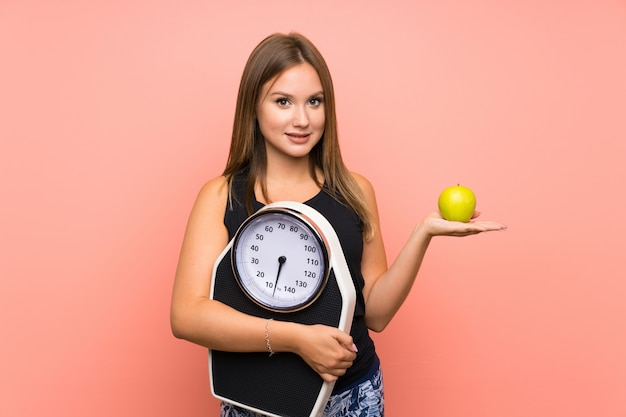 Teenager girl with weighing machine over isolated