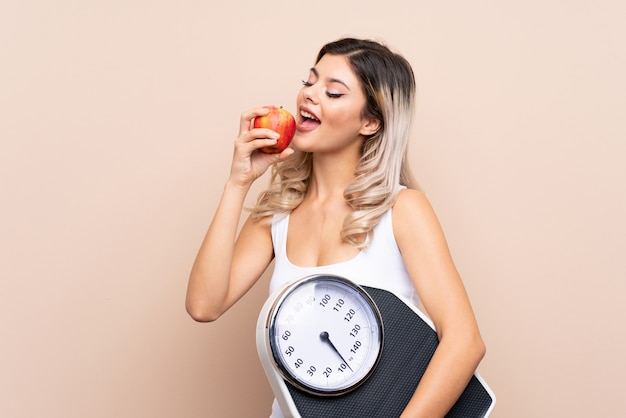 Teenager girl with weighing machine with weighing machine and with an apple