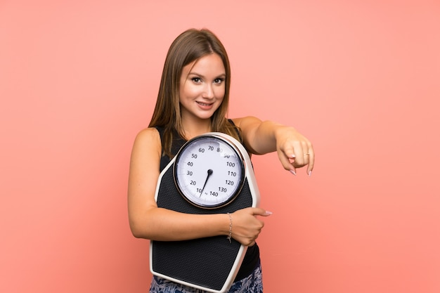 Teenager girl with weighing machine