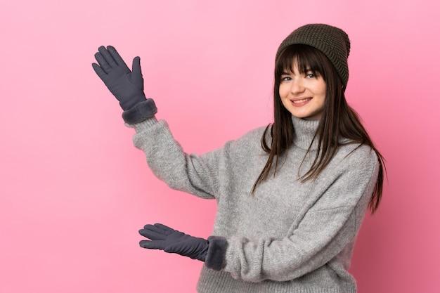 겨울 모자와 십 대 소녀는 올 초대에 대 한 측면에 손을 확장 흰색 절연