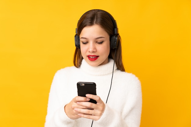 Teenager girl on yellow wall listening music and looking to mobile