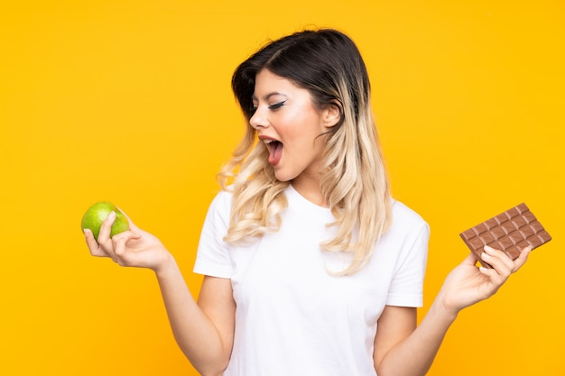Teenager girl on yellow wall taking a chocolate tablet in one hand and an apple in the other