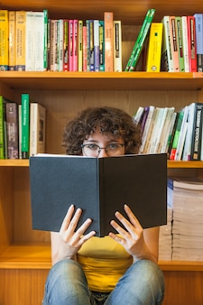Teenager in glasses covering face with book