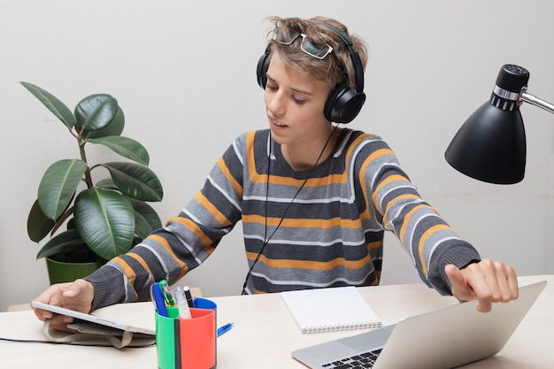 Teenager in glasses and headphones studying online