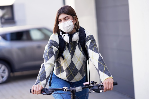 A teenager going to school by bike and wearing a face mask due to coronavirus pandemic
