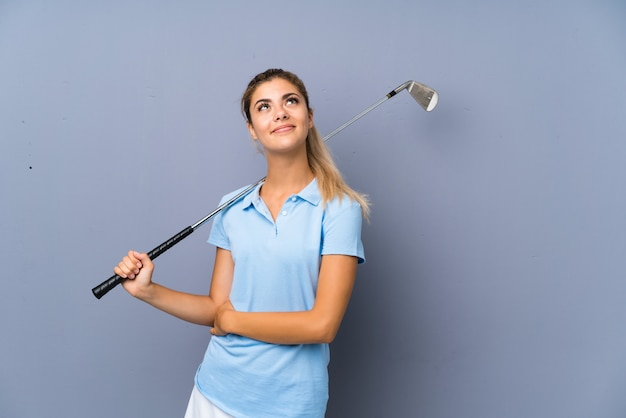 Teenager golfer girl over grey wall looking up while smiling