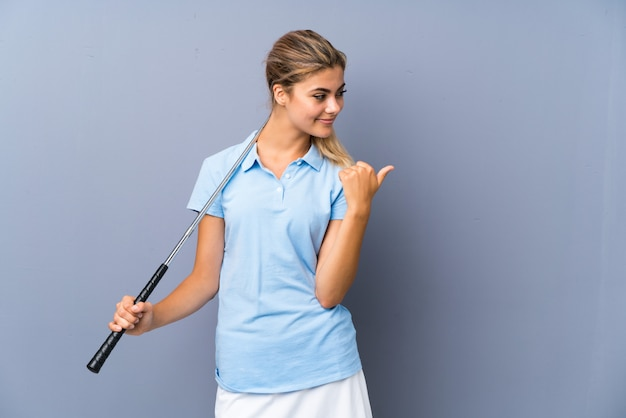 Teenager golfer girl over grey wall pointing to the side to present a product