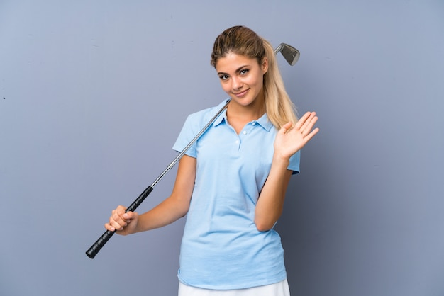 Teenager golfer girl over grey wall saluting with hand with happy expression