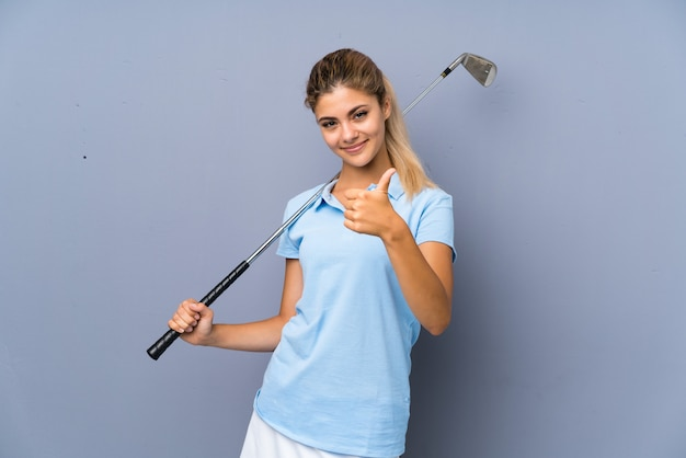 Teenager golfer girl over grey wall with thumbs up because something good has happened