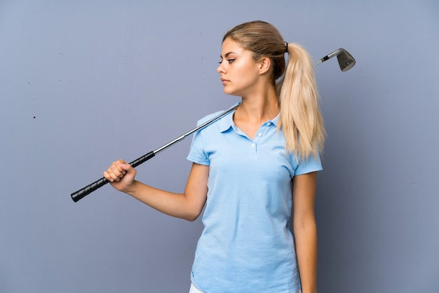 Teenager golfer girl over grey wall