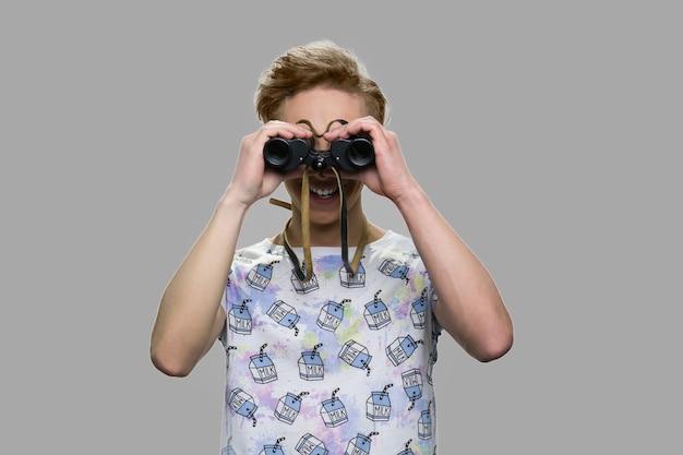 쌍안경을 통해 찾고 십 대 남자입니다. 미래와 관점 개념.