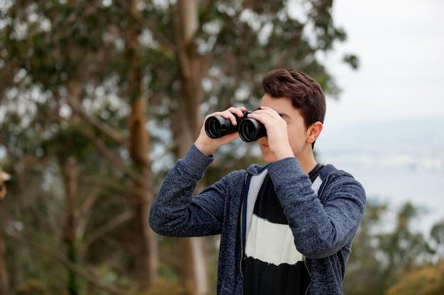 双眼鏡で探しているティーンエイジャーの男