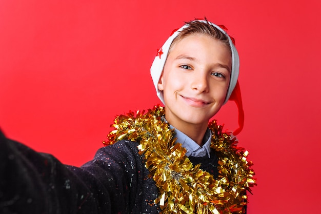 A teenager guy takes a selfie in a santa hat and tinsel on the neck