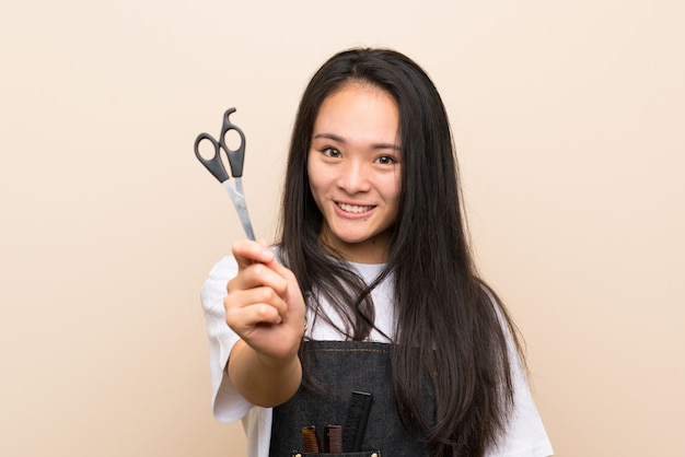 Teenager hairdresser girl over isolated wall