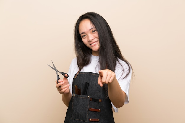 Teenager hairdresser girl points finger at you with a confident expression