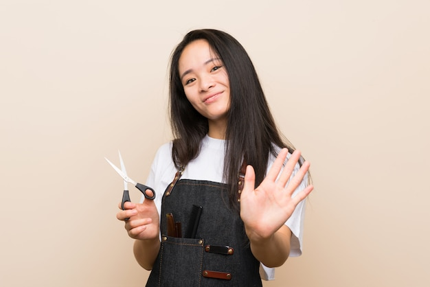 Teenager hairdresser girl saluting with hand with happy expression
