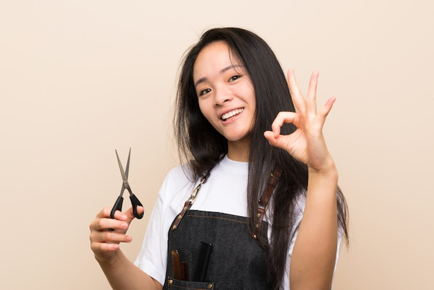 Teenager hairdresser girl showing ok sign with fingers