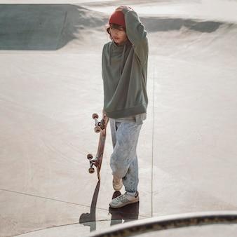 Подросток весело катается на скейтборде на открытом воздухе в парке