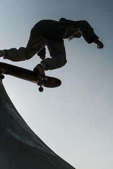 Подросток развлекается со скейтбордом в парке на улице