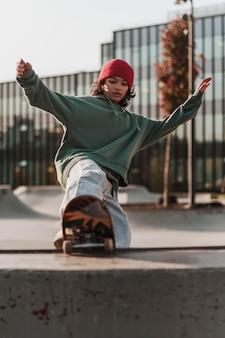 Подросток развлекается со скейтбордом в парке