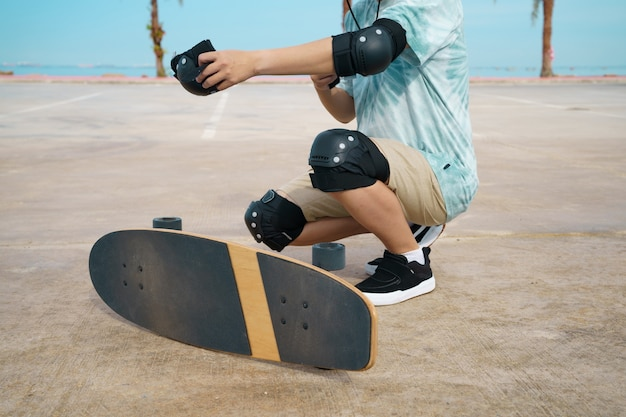 Teenager having fun with skateboard and using protection around city