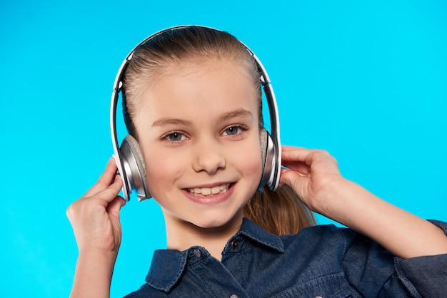 Teenager in headphones with pleasure listens to music.