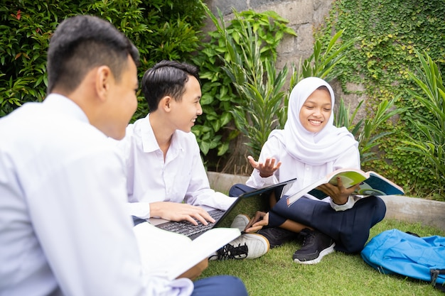A teenager in a headscarf and two teenage boys in school uniforms using a laptop and a book while st...