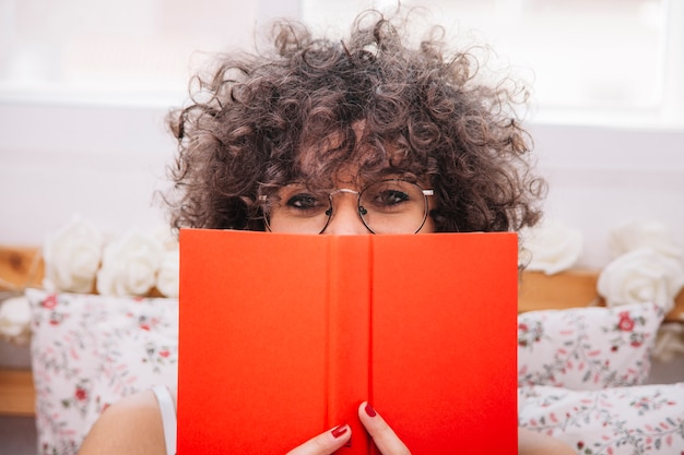 Teenager hiding face behind book
