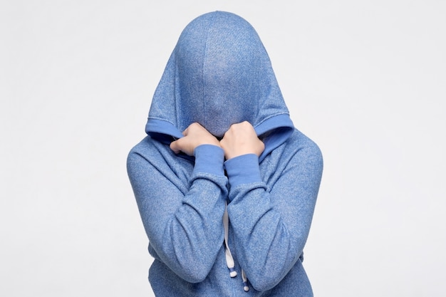 Teenager hiding her face being frightened and stressed