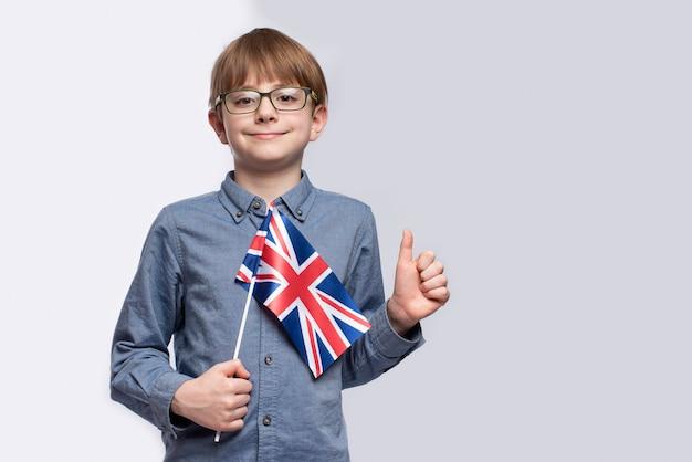 Подросток держит в руках флаг великобритании и показывает жест хорошо выполненной работы. изучение английского языка. образование в британии.