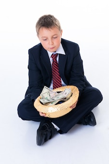 A teenager holding a hat and begging.