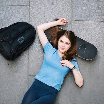 Teenager holding head on skateboard
