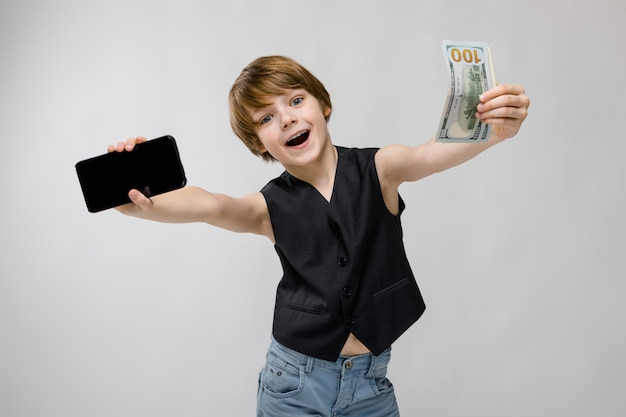 A teenager holds a phone in one hand, and in another money. charming teenager with blond hair and dark eyes. teenager is happy