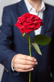 A teenager holds a red rose in his hand. the boy is dressed in a blue suit and white shirt. close-up.