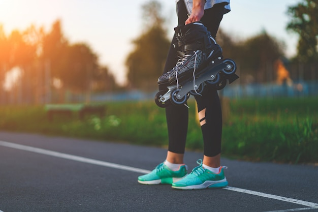 Teenager holds roller skates for inline skating outdoors.