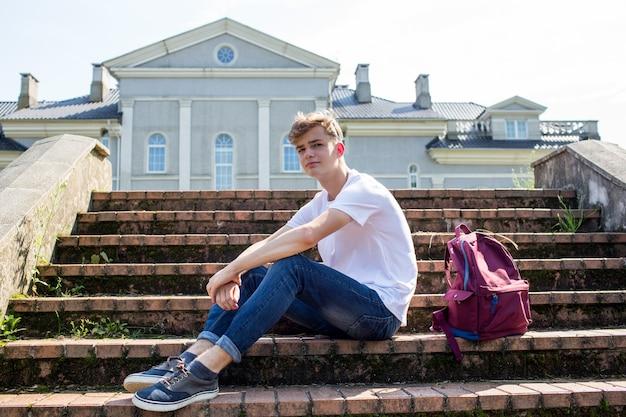 Подросток в белой футболке со школьным рюкзаком сидит на ступеньках в парке