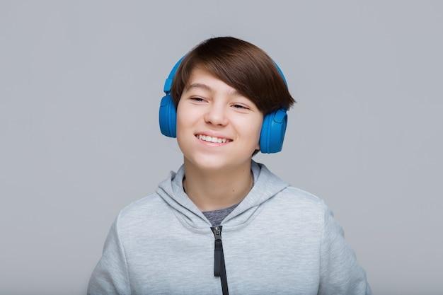 Подросток в синих наушниках слушает музыку