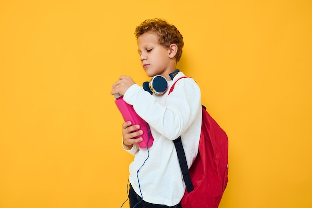 Подросток в наушниках бутылка с водой желтом фоне. фото высокого качества