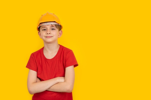 黄色の壁に保護ヘルメットのティーンエイジャー