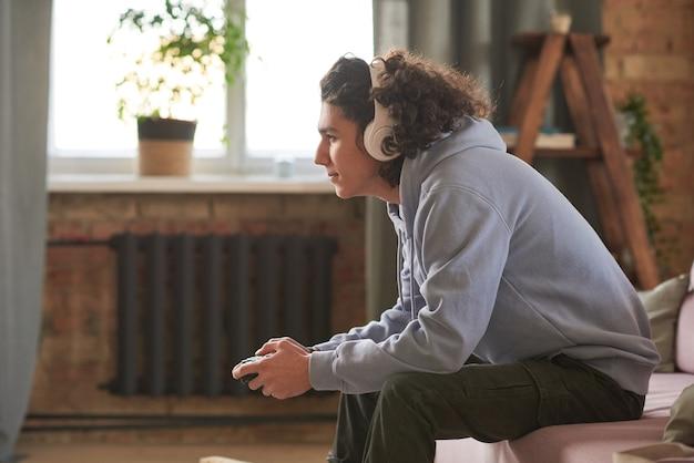 ソファに座って部屋でビデオゲームをプレイするワイヤレスヘッドフォンのティーンエイジャー